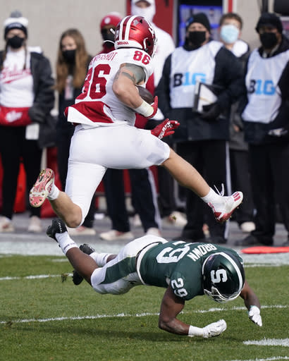 Indiana tight end Peyton Hendershot (86) jumps over Michigan State cornerback Shakur Brown (29) during the first half of an NCAA college football game, Saturday, Nov. 14, 2020, in East Lansing, Mich. (AP Photo/Carlos Osorio)