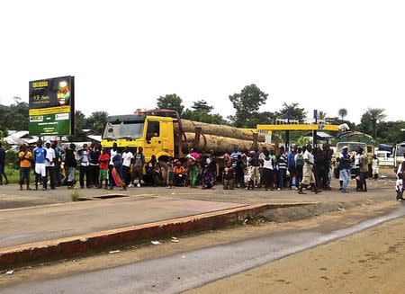 A crowd gathers near a checkpoint, which controls the movement of people in and out of Ebola-hit regions, at the entrance to Bomi county in northwestern Liberia