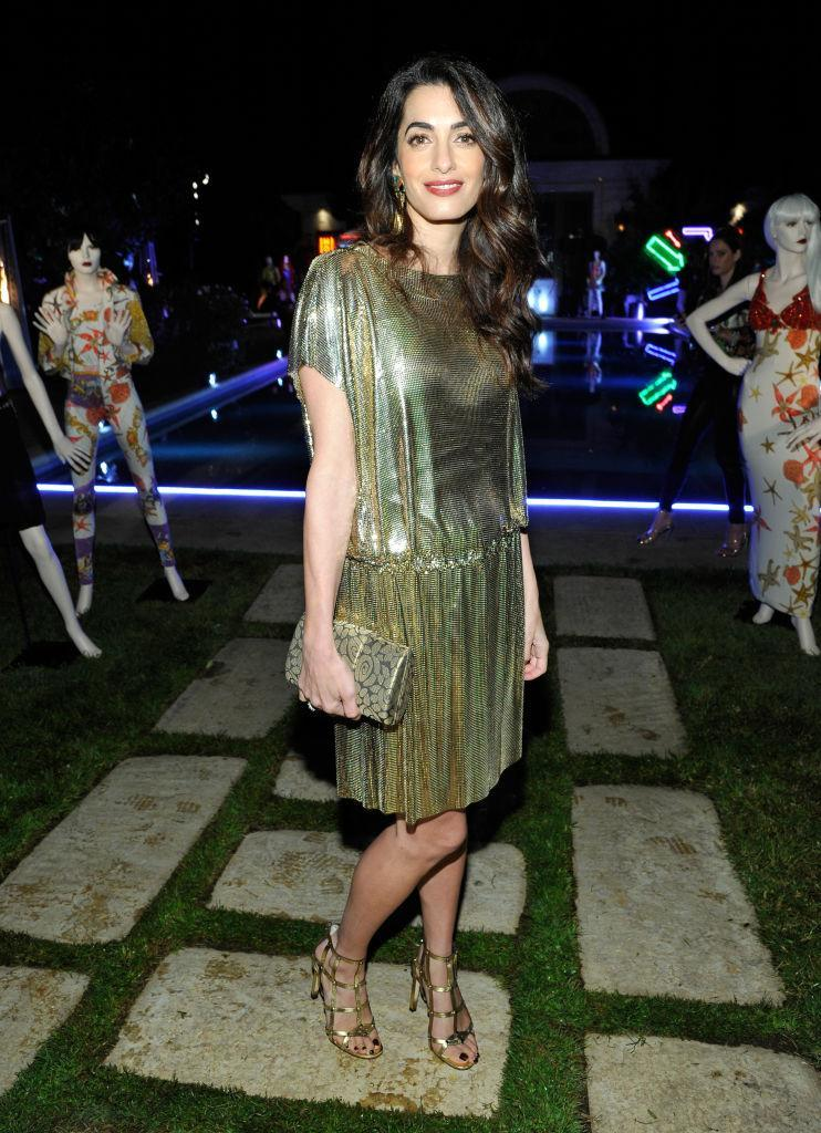 """<p><strong>When: October 5, 2017</strong><br>On Thursday night, Amal Clooney showed off her amazing post-baby body while paying tribute to the late Gianni Versace on the 20th anniversary of his death at the Farfetch and William-Vintage party in LA. Amal stood out from the crowd in vintage gold mesh that was slightly reminiscent of a roaring '20s flapper dress. The dress was designed by Gianni's sister, Donatella Versace, and was created out of the """"<a href=""""https://www.instagram.com/p/BZWrAERDD7M/?taken-by=versace_official"""" rel=""""nofollow noopener"""" target=""""_blank"""" data-ylk=""""slk:dazzling metal mesh"""" class=""""link rapid-noclick-resp"""">dazzling metal mesh</a>"""" Versace was known for. Amal smartly paired the dress with a matching clutch and strappy heels. (<em>Photo: Getty)</em> </p>"""