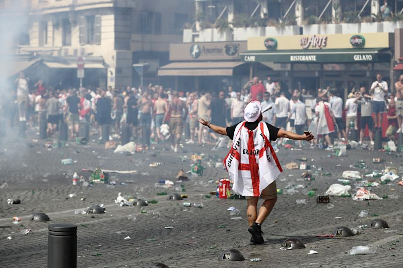 MARSEILLE, FRANCE - JUNE 11: A fan wears the Englad flag colors as rubbish lines the streets as England fans gather, cheer and clash with police ahead of the game against Russia later today on June 11, 2016 in Marseille, France. Football fans from around Europe have descended on France for the UEFA Euro 2016 football tournament. (Photo by Carl Court/Getty Images)