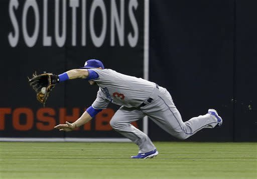 Los Angeles Dodgers left fielder Skip Schumaker makes a diving catch to rob San Diego Padres' Mark Kotsay of a base hit with two runners on base in the eighth d inning of a baseball game in San Diego, Wednesday, April 10, 2013. (AP Photo/Lenny Ignelzi)