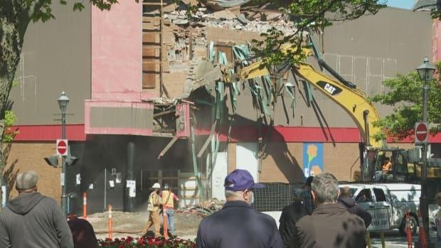 Dozens of people gathered Wednesday morning to watch the demolition, some with fond memories of shopping at the once popular Woolworth's.