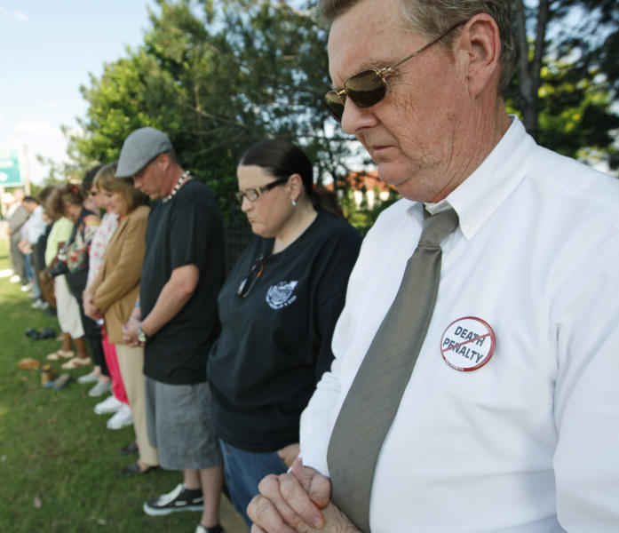 Dane Gill, right, participates in a silent vigil outside the Governor's Mansion in Oklahoma City, Tuesday, May 1, 2012, in protest of the execution of Michael Bascum Selsor. An Oklahoma man convicted of murdering a Tulsa convenience store manager almost 37 years ago was executed by lethal injection Tuesday. (AP Photo/Sue Ogrocki)