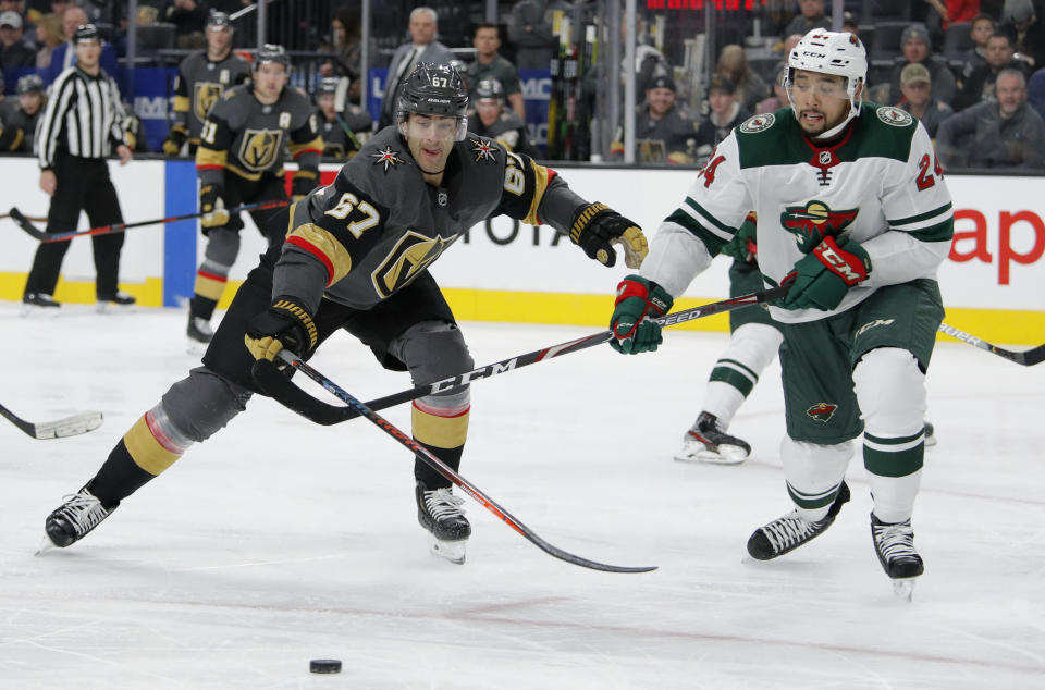 Vegas Golden Knights left wing Max Pacioretty (67) and Minnesota Wild defenseman Matt Dumba (24) vie for the puck during the second period of an NHL hockey game Tuesday, Dec. 17, 2019, in Las Vegas. (AP Photo/John Locher)