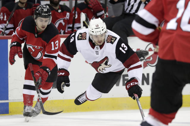Arizona Coyotes center Vinnie Hinostroza, right, goes airborne while competing for the puck with New Jersey Devils center Nico Hischier, of Switzerland, during the first period of an NHL hockey game, Saturday, March 23, 2019, in Newark, N.J. (AP Photo/Julio Cortez)