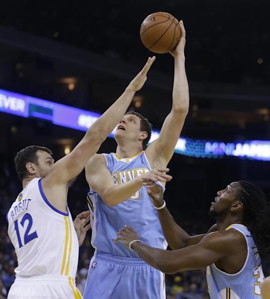 Denver Nuggets' Timofey Mozgov, center, shoots over Golden State Warriors' Andrew Bogut (12) during the first half of an NBA basketball game Thursday, April 10, 2014, in Oakland, Calif. (AP Photo/Ben Margot)