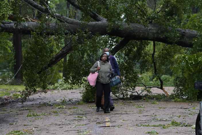 Northeast Jackson, Miss., residents leave their powerless home after utility lines were brought down by trees and debris spread by high winds Tuesday, May 4, 2021. The severe weather was not unexpected, since the state was hit with a number of tornadoes on Sunday. (AP Photo/Rogelio V. Solis)