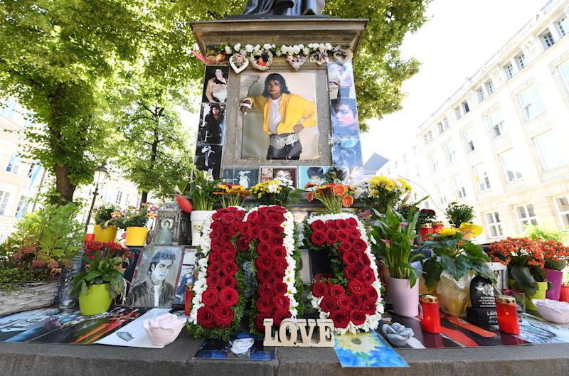 """24 June 2019, Bavaria, Munich: The letters """"MJ"""" are surrounded by flowers, pictures and candles before the commemoration of the 10th anniversary of Michael Jackson's death at his memorial at Promenadeplatz. The makers of the Jackson musical """"Beat it"""" have invited friends and companions to the Bavarian Court. Among other things the """"Michael-Jackson""""-Suite will be visited, where the """"King of Pop"""" lived when he was in Munich. Photo: Tobias Hase/dpa (Photo by Tobias Hase/picture alliance via Getty Images)"""