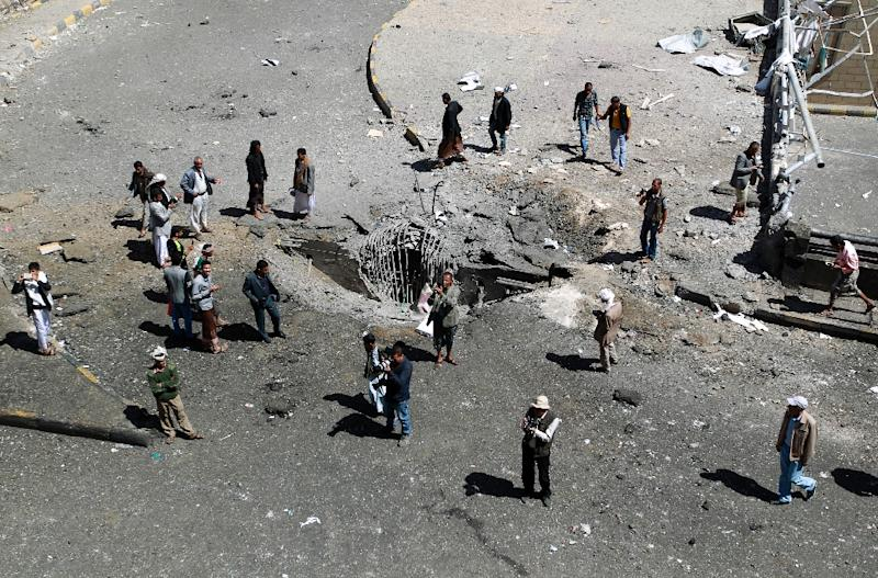 Yemenis stand around a crater reportedly caused by air strikes carried out by the Saudi-led coalition in the capital Sanaa on October 1, 2015 (AFP Photo/Mohammed Huwais)