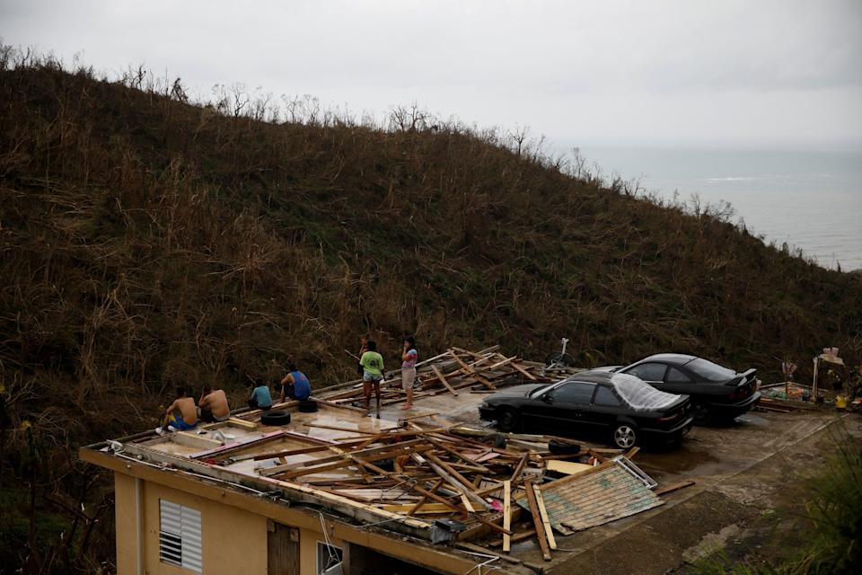 People stay at the roof of a damaged house after the area was hit by Hurricane Maria in Yabucoa, Puerto Rico September 22, 2017. REUTERS/Carlos Garcia Rawlins     TPX IMAGES OF THE DAY