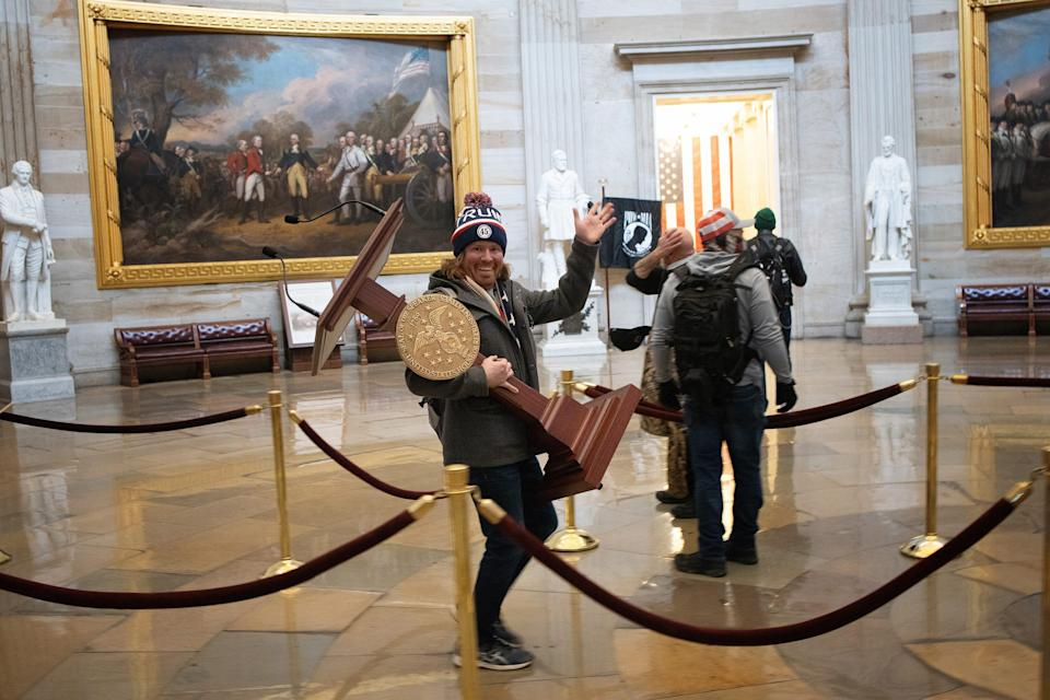 Adam Christian Johnson, carries the lectern of U.S. Speaker of the House Nancy Pelosi through the Roturnda of the U.S. Capitol Building after a pro-Trump mob stormed the building.