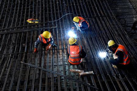 Workers weld steel bars at the construction site of a Tencent data center in a tunnel in Guian