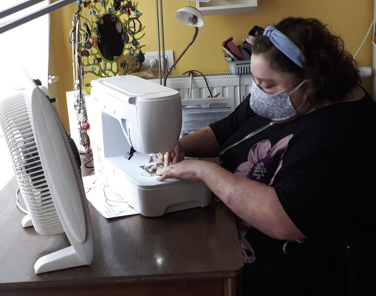 In this photo taken on Thursday, March 19, 2020, Sien Lagae, works on a mouth mask, meant to help protect from the spread of COVID-19, on her sewing machine at home in Torhout, Belgium. Lagae runs a social media group of volunteers who are making mouth masks for family and friends as well as hospital and caregivers in Belgium due to a shortage in supply of industrially made masks. For most people, the new coronavirus causes only mild or moderate symptoms, such as fever and cough. For some, especially older adults and people with existing health problems, it can cause more severe illness, including pneumonia.(Sien Lagae via AP)