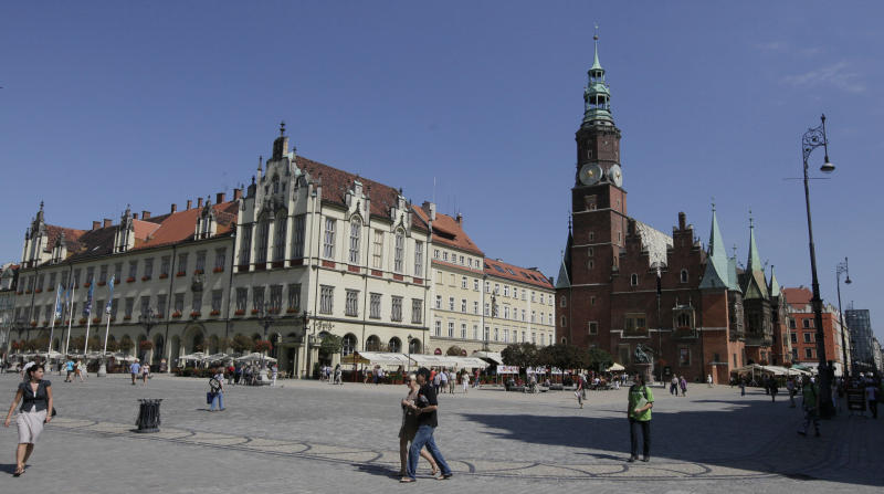 Tourists walk through the main square with the Town Hall on the right in Wroclaw, Poland, in this  Aug. 18, 2011 photo. The latest backdrop for European financial crisis talks was Wroclaw, Poland _ or Breslau, as the picturesque city on the Oder River is still known in Germany. As Europe's finance chiefs bounce from meeting to meeting trying to hash out a strategy to contain their debt troubles, the city's history may serve as a reminder of what is at stake: a hard-won European unity that followed centuries of ravaging wars and has slowly enveloped the former Communist states in the continent's east.  (AP Photo/Czarek Sokolowski)