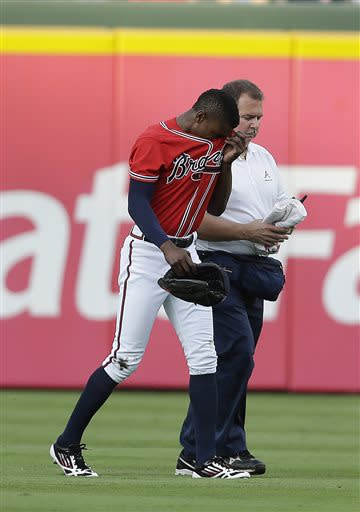 Atlanta Braves center fielder B.J. Upton, left, is helped off the field by trainer Jim Lovell after being injured while diving for a ball in the first inning of a baseball game against the Cincinnati Reds, Friday, July 12, 2013, in Atlanta. (AP Photo/John Bazemore)