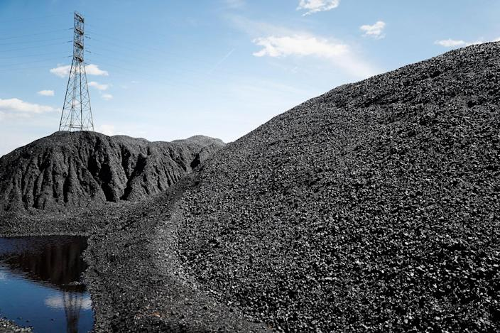 <p>Piles of coal rest at a facility along the Ohio River as power transmission lines stand in the background, Friday, April 7, 2017, in Cincinnati, Ohio. (AP Photo/John Minchillo) </p>