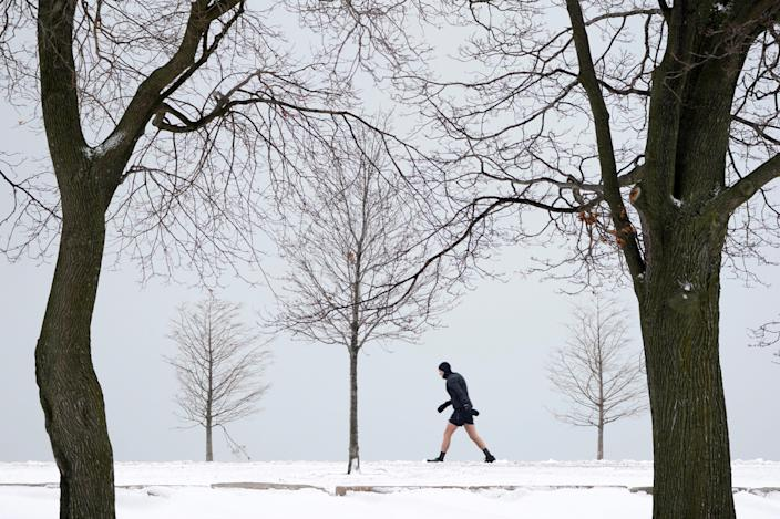 A lone runner leans into a stiff wind near Lake Michigan on the Northside of Chicago Tuesday, Jan. 26, 2021. A major winter storm dumped more than a foot of snow on parts of the middle of the country stretching from central Kansas northeast to Chicago and southern Michigan.