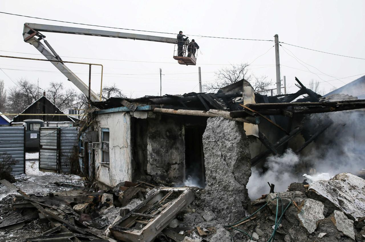 """Repairmen work to repair the electricity network after what locals say was a night shelling in Donetsk December 9, 2014. Ukrainian government forces said they had suspended combat operations as a """"Day of Silence"""" began in the war-torn east on Tuesday, marking an effective ceasefire on the front line of the conflict with separatist rebels. In the city of Donetsk, the separatists main stronghold, a firing was heard up to 9 a.m. but later appeared to have slackened off. REUTERS/Maxim Shemetov (UKRAINE - Tags: CIVIL UNREST CONFLICT MILITARY)"""