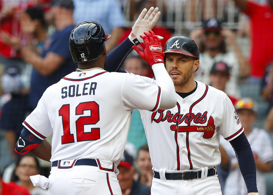 ATLANTA, GA - AUGUST 07: Jorge Soler #12 of the Atlanta Braves reacts with Freddie Freeman #5 after hitting a solo home run in the first inning of an MLB game against the Washington Nationals at Truist Park on August 7, 2021 in Atlanta, Georgia. (Photo by Todd Kirkland/Getty Images)