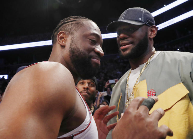Miami Heat guard Dwyane Wade, left, chats with LeBron James before the Heat's NBA basketball game against the Brooklyn Nets, Wednesday, April 10, 2019, in New York. Wade is retiring after the game. (AP Photo/Kathy Willens)