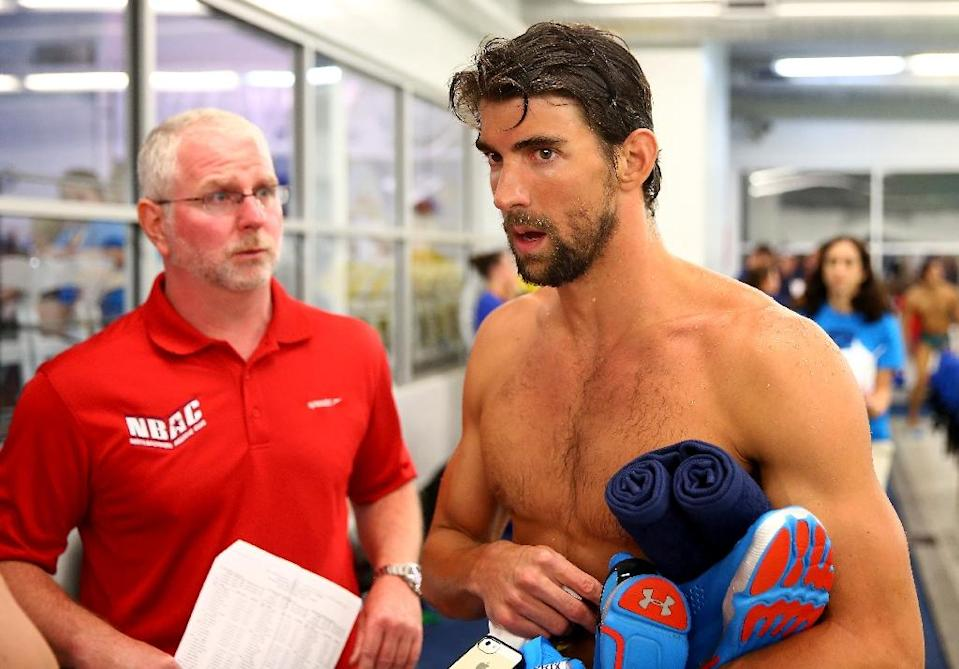 Coach Bob Bowman (L) and Michael Phelps talk during day 1 of the Arena Grand Prix on May 16, 2014 in Charlotte, North Carolina (AFP Photo/Streeter Lecka)