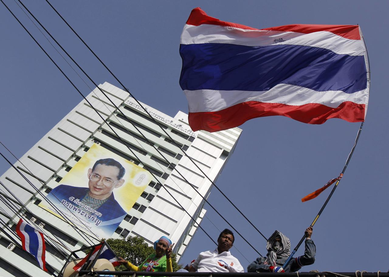 An anti-government protester waves a Thai national flag during a rally outside the Ministry of Natural Resources and Environment in Bangkok