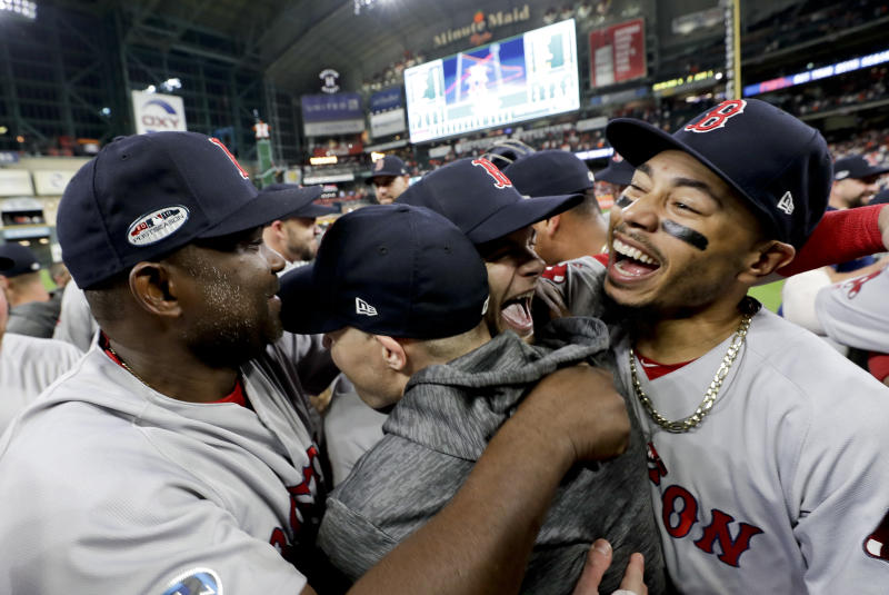 Boston Red Sox right fielder Mookie Betts, right, celebrates after they won the baseball American League Championship Series against the Houston Astros on Thursday, Oct. 18, 2018, in Houston. Red Sox won 4-1. (AP Photo/David J. Phillip)
