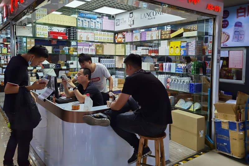 Cosmetics sellers check an order with a customer at the Mingtong Digital City market in Shenzhen's Huaqiangbei area