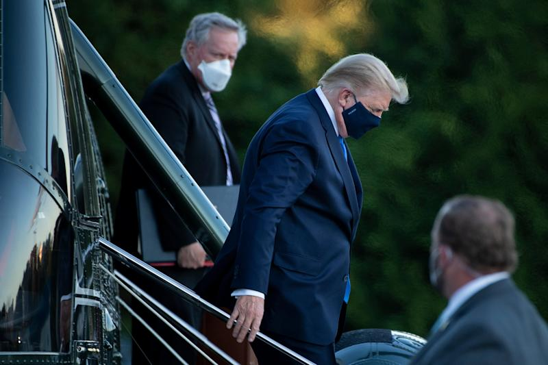 White House Chief of Staff Mark Meadows (L) watches as US President Donald Trump (C) walks off Marine One while arriving at Walter Reed Medical Center in Bethesda, Maryland on October 2, 2020. - President Donald Trump will spend the coming days in a military hospital just outside Washington to undergo treatment for the coronavirus, but will continue to work, the White House said Friday (Photo by Brendan Smialowski / AFP) (Photo by BRENDAN SMIALOWSKI/AFP via Getty Images)