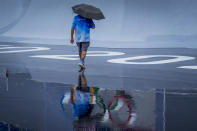 A venue official takes a look at the BMX Freestyle course after a training session was canceled due to rain, at the 2020 Summer Olympics, Tuesday, July 27, 2021, in Tokyo, Japan. (AP Photo/Ben Curtis)