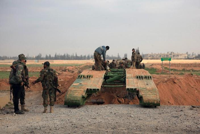 Members of the government forces install a retractable military bridge to cross a trench on the eastern outskirts of Syria's northern city of Aleppo on February 21, 2016 (AFP Photo/George Ourfalian)
