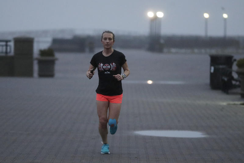 In this Wednesday, April 4, 2018, photo Amelia Gapin works out in early morning fog while preparing to run the Boston Marathon during a jog at Liberty State Park in Jersey City, N.J. Boston Marathon organizers say transgender runners can qualify for the race using the gender they identify with. Gapin, a transgender woman from New Jersey, says running Boston this year will be a victory lap for what she has accomplished. (AP Photo/Julio Cortez)