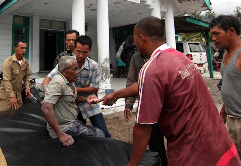 Acenese men assist an earthquake victim to receive medical treatment outside a community health center in Bener Meriah, Aceh province, Indonesia, Tuesday, July 2, 2013. The magnitude-6.1 quake struck at a depth of just 10 kilometers (6 miles) and was centered 55 kilometers (34 miles) west of the town of Bireun on the western tip of Sumatra island, the U.S. Geological Survey said. (AP Photo/Ahmad Ariska)