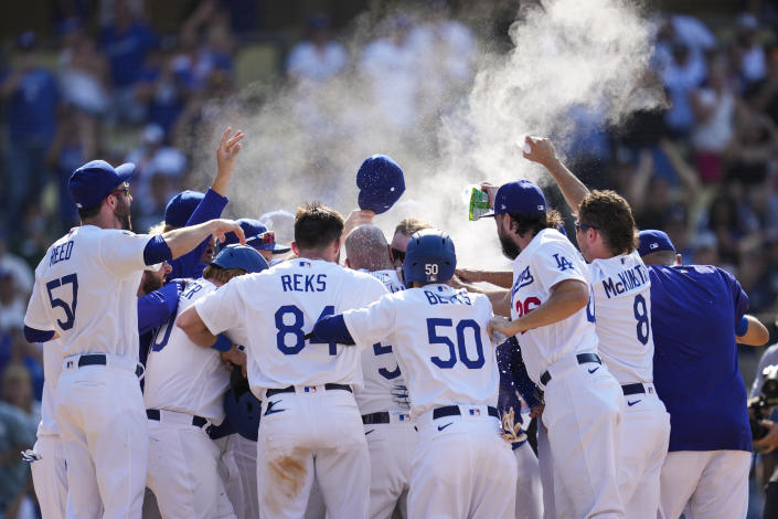 The Los Angeles Dodgers celebrate after Max Muncy hit a home run during the ninth inning of a baseball game against the Arizona Diamondbacks Sunday, July 11, 2021, in Los Angeles. Zach Reks and Mookie Betts also scored. The homer won the game for the Dodgers 7-4. (AP Photo/Ashley Landis)