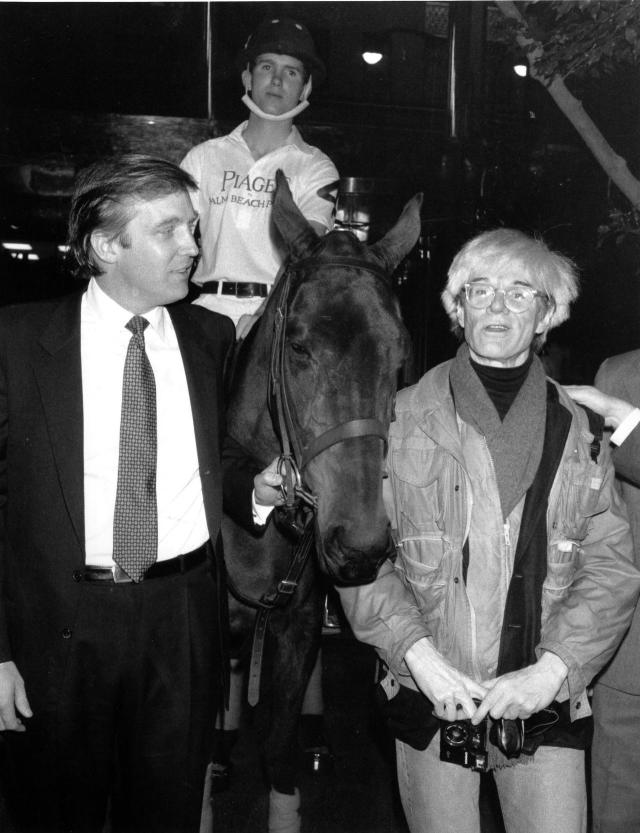 <p>Donald holds the bridle of a polo pony while talking to Andy Warhol on Nov. 4, 1983. Yale University polo player Eric Stever sits astride the horse. <i>(Photo: Mario Suriani/AP)</i> </p>