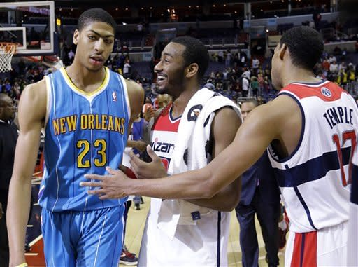 New Orleans Hornets forward Anthony Davis (23) reacts with Washington Wizards guard John Wall, center, and guard Garrett Temple right, after an NBA basketball game Friday, March 15, 2013 in Washington. The Wizards won 96-87. (AP Photo/Alex Brandon)