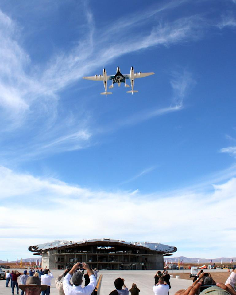 In this Oct. 22, 2010, image, Virgin Galactic's WhiteKnightTwo jet-powered carrier aircraft flies over Spaceport America during a runway dedication ceremony in Upham, N.M. Virgin Galactic founder Richard Branson has vowed to be one of the first passengers when the company begins commercial space tourism flights from the spaceport.