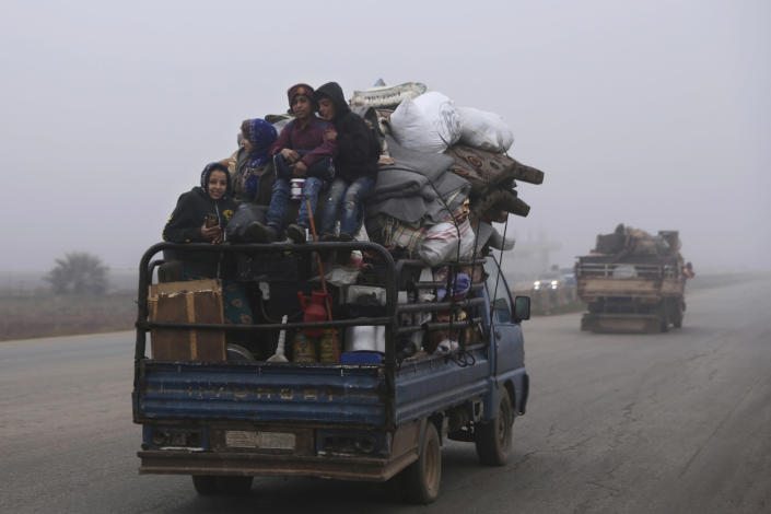 FILE - This Dec. 23, 2019, file photo, civilians ride in a truck as they flee Maaret al-Numan, Syria, ahead of a government offensive. The M5 highway, recaptured by President Bashar Assad's forces, is arguably the most coveted prize in Syria's civil war. The strategic highway is vital for Syria's economy as well as for moving troops. (AP Photo/Ghaith Alsayed, File)