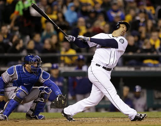 Texas Rangers catcher A.J. Pierzynski catches the ball as Seattle Mariners' Raul Ibanez swings and misses to strike out with two outs and the bases loaded in the seventh inning of a baseball game Thursday, April 11, 2013, in Seattle. (AP Photo/Elaine Thompson)