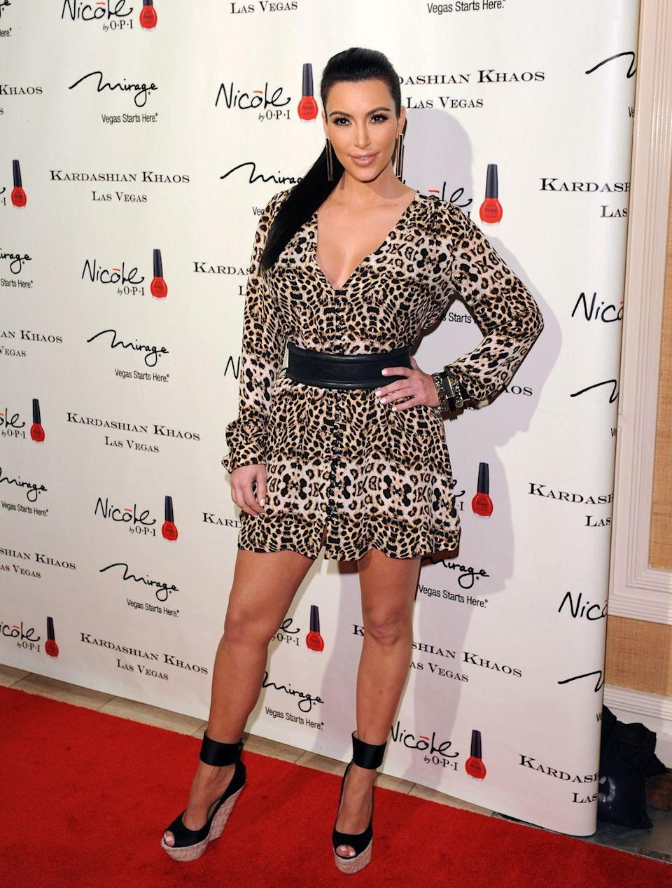 <p>Kim Kardashian paired her sky-high espadrilles with a ruffled cheetah-print dress cinched at the waist for the grand opening of the Kardashian Khaos store in Las Vegas.</p>