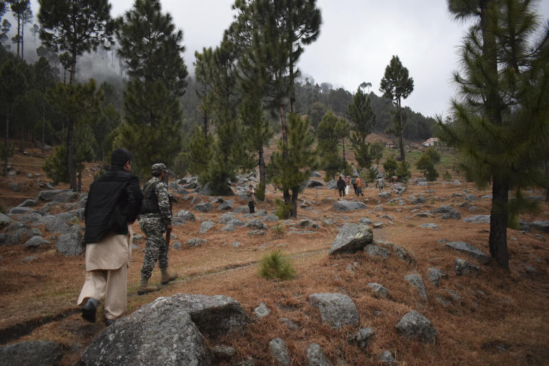 """Pakistani reporters and troops visit the site of an Indian airstrike in Jaba, near Balakot, Pakistan, Tuesday, Feb. 26, 2019. Pakistan said India launched an airstrike on its territory early Tuesday that caused no casualties, while India said it targeted a terrorist training camp in a pre-emptive strike that killed a """"very large number"""" of militants. (AP Photo/Aqeel Ahmed)"""