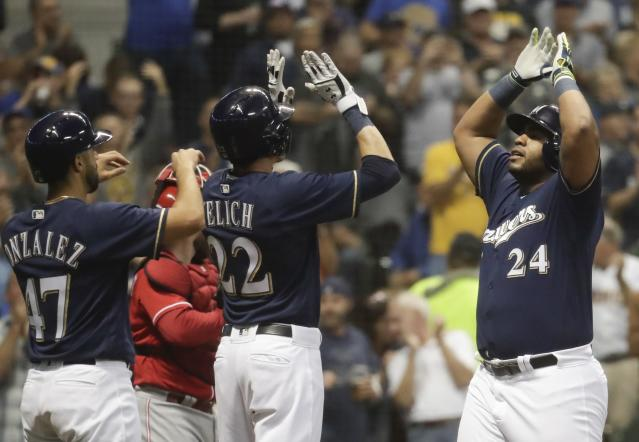 Milwaukee Brewers' Jesus Aguilar celebrates after hitting a three-run home run during the third inning of a baseball game against the Cincinnati Reds Wednesday, Sept. 19, 2018, in Milwaukee. (AP Photo/Morry Gash)