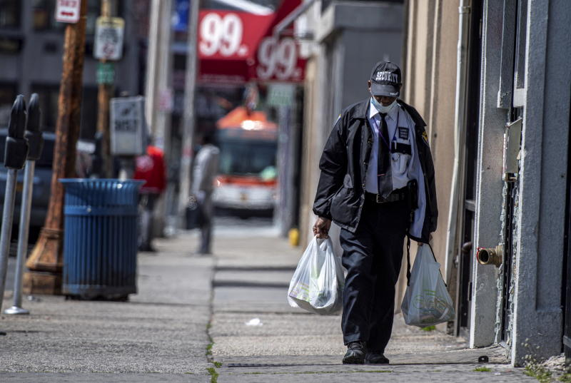 Hempstead, N.Y.: A man wearing a security guard uniform and a mask due to coronavirus concerns walks down a street carrying groceries in Hempstead, New York on April 8, 2020. (Photo by J. Conrad Williams Jr./Newsday via Getty Images)