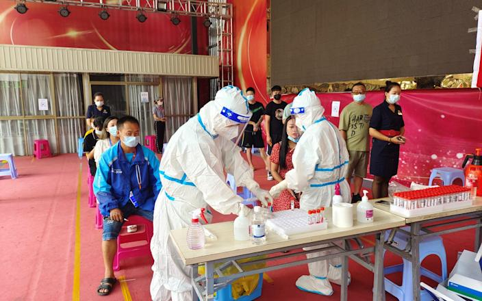 People line up for nucleic acid testing at a residential compound in Ruili - via Reuters