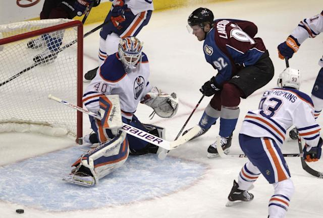 Edmonton Oilers goalie Devan Dubnyk (40) deflects a shot by Colorado Avalanche left wing Gabriel Landeskog (92) as Oilers center Ryan Nugent-Hopkins (93) watches during the first period of an NHL hockey game in Denver, Thursday, Dec. 19, 2013. (AP Photo/Joe Mahoney)