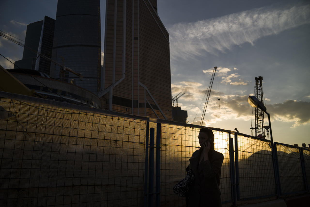 <p>A woman walks along a fence next to Moscow's skyscrapers during sunset in Moscow, May 18, 2017. (Photo: Alexander Zemlianichenko/AP) </p>