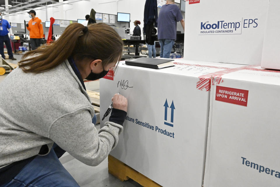 Melissa Owens, operations plant manager for the McKesson Corporation, signs the first shipping box of the Johnson & Johnson COVID-19 vaccine at the McKesson facility in Shepherdsville, Ky., Monday, March 1, 2021. (AP Photo/Timothy D. Easley, Pool)