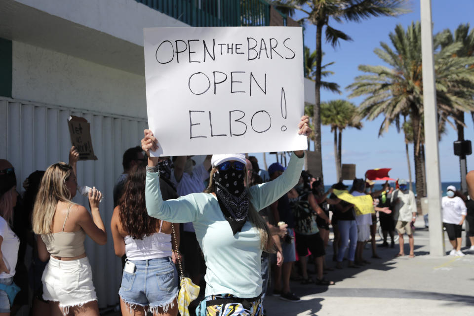 """A woman participates in a """"Right to Work"""" rally outside of the Elbo Room bar , which remains closed, during the new coronavirus pandemic, Tuesday, June 16, 2020, in Fort Lauderdale, Fla. Across Florida, bars were part of the Phase 2 reopenings that occurred earlier in June, except in three counties in South Florida. (Lynne Sladky/AP)"""