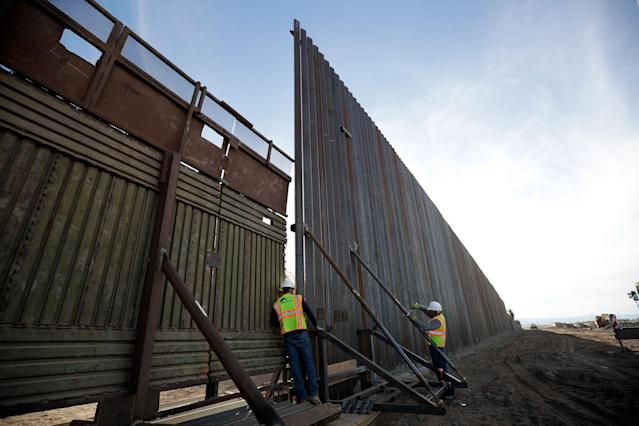 <p>A worker looks between the first section of a newly-constructed structure along the border separating Mexicali, Mexico and Calexico, Calif., March 5, 2018. (Photo: Gregory Bull/AP) </p>