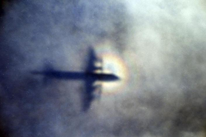 FILE - In this March 31, 2014 file photo, the shadow of a Royal New Zealand Air Force P3 Orion is seen on low level cloud while the aircraft searches for missing Malaysia Airlines Flight MH370 in the southern Indian Ocean, near the coast of Western Australia. After nearly three years, the hunt for Malaysia Airlines Flight 370 ended in futility and frustration on Tuesday, Jan. 17, 2017, as crews completed their deep-sea search of a desolate stretch of the Indian Ocean without finding a single trace of the plane. (AP Photo/Rob Griffith, File)